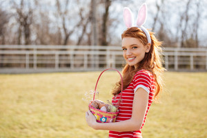 Happy cheerful girl wearing bunny ears and holding easter basket with painted eggs outdoors