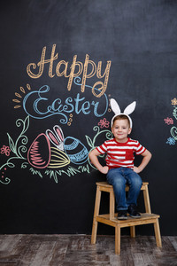 Happy cheerful little boy wearing bunny ears and celebrating easter over chalk board with colorful text background