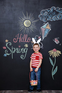 Happy cheerful little boy wearing bunny ears and holding easter basket full of eggs over chalk board with colorful text background