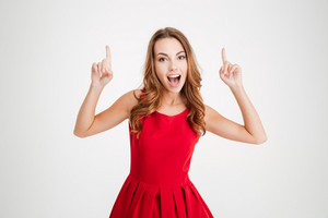 Happy cheerful woman in red dress pointing fingers up and looking at camera isolated over white background