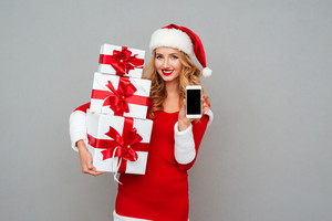 Happy cheerful woman in red santa claus outfit showing blank screen mobile phone isolated on the gray background