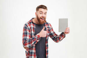 Happy cheerful young man in plaid shirt holding book and showing thumb up over white background