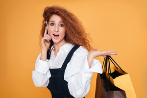 Happy confused young woman holding shopping bags and talking on mobile phone