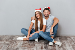 Happy couple in christmas hats are cuddling. very pretty. gray background