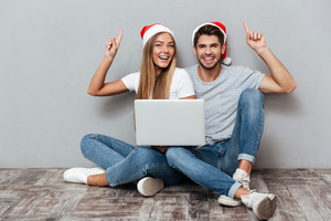 Happy couple in christmas hats with laptop. sitting down. beautiful models