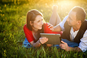 Happy couple is lying on the grass and playing with tablet