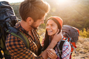Happy couple with backpacks in the mountains. eyes to eye