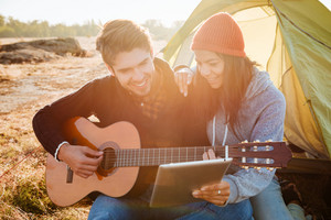 Happy couple with guitar near the tent. close up image