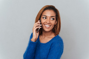 Happy cute african woman in blue sweater talking at phone and looking aside. Isolated gray background
