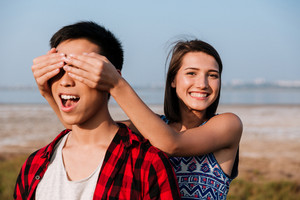 Happy cute young woman covered eyes by hands to her boyfriend outdoors