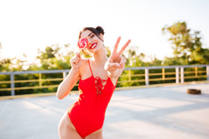 Happy cute young woman covered her eye with lollipop and showing peace sign standing outdoors