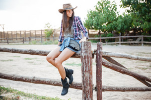Happy cute young woman cowgirl sitting on fence