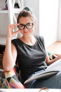 Happy cute young woman in glasses reading book at home