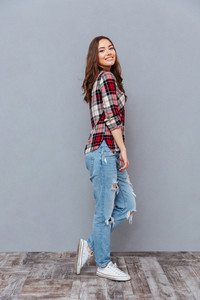 Happy cute young woman in plaid shirt and jeans standing and posing