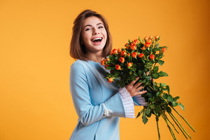 Happy cute young woman laughing and holding bunch of roses over yellow background