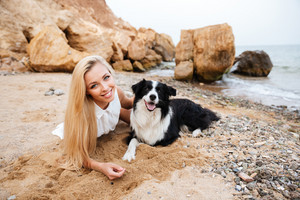 Happy cute young woman relaxing and smiling with her dog on the beach