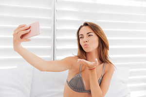 Happy cute young woman sending a kiss and taking selfie with smatphone over white background