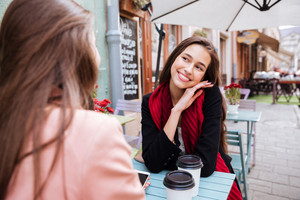 Happy cute young woman smiling and talking to her friend in outdoor cafe