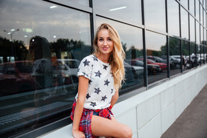 Happy cute young woman with blonde hair standing outdoors at the glass building