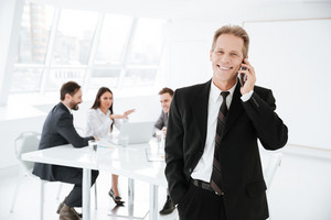 Happy Elderly Business man talking at phone in office with colleagues on background
