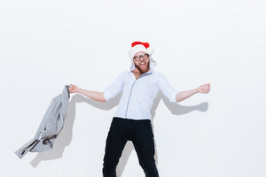 Happy excited bearded young man in santa claus hat holding jacket and having fun over white background