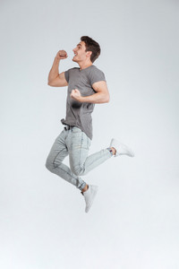 Happy excited cheerful young man jumping and celebrating success over white background