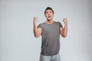 Happy excited man screaming and celebrating succcess with two fists up over white background