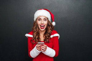 Happy excited woman in red santa claus outfit with mobile phone over black background