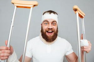 Happy excited young man holding crutches and laughing over white background