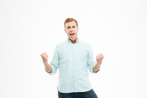 Happy excited young man standing and celebrating success over white background