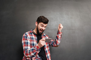 Happy excited young man using cell phone and celebrating success over grey background