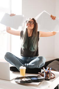 Happy excited young woman sitting on the table and celebrating success