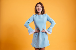 Happy excited young woman standing with hands on waist over yellow background