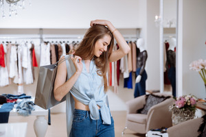 Happy excited young woman with shopping bags in clothing store