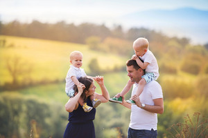 Happy family enjoying life together at meadow outdoor.