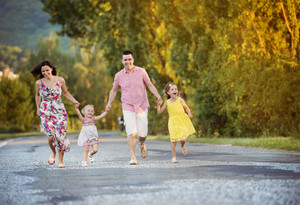 Happy family having fun during the walk on the road