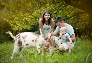 Happy family is relaxing in green meadow with goat