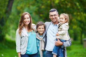 Happy family members looking at camera in natural environment