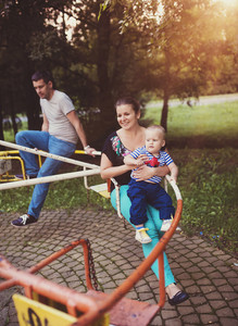 Happy family outside in a park on an old carousel.