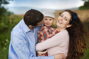 Happy family playing with son on the meadow