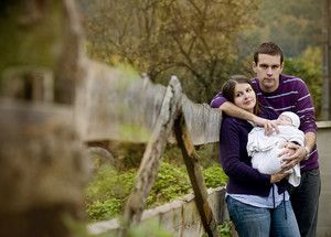 Happy family spending time with newborn baby in nature