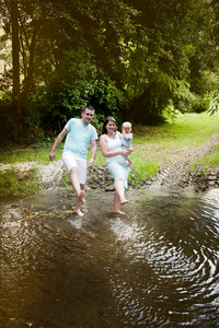 Happy family with little baby boy is splashing water in the river