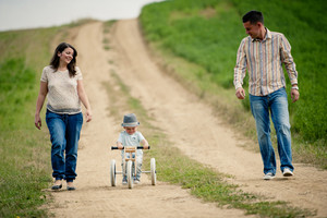 Happy family with little boy on wooden tricycle walking in ntaure