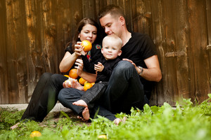 Happy family with little boy sitting by the wooden fence and having fun with oranges