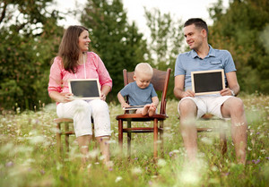Happy family with little boy sitting on chairs and holding little blackboards in the meadow