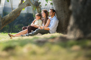Happy family with man, woman and child leaning on tree in city park. Copy space
