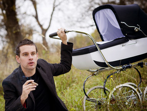 Happy father with baby in vintage pram relaxing together golden and colorful autumn nature