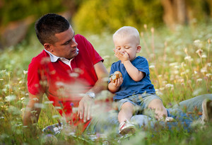 Happy father with little son sitting on meadow in summer and eating muffins