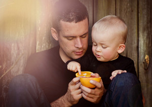 Happy father with son eating orange and by the wooden fence