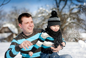 Happy father with son having fun outside in snow